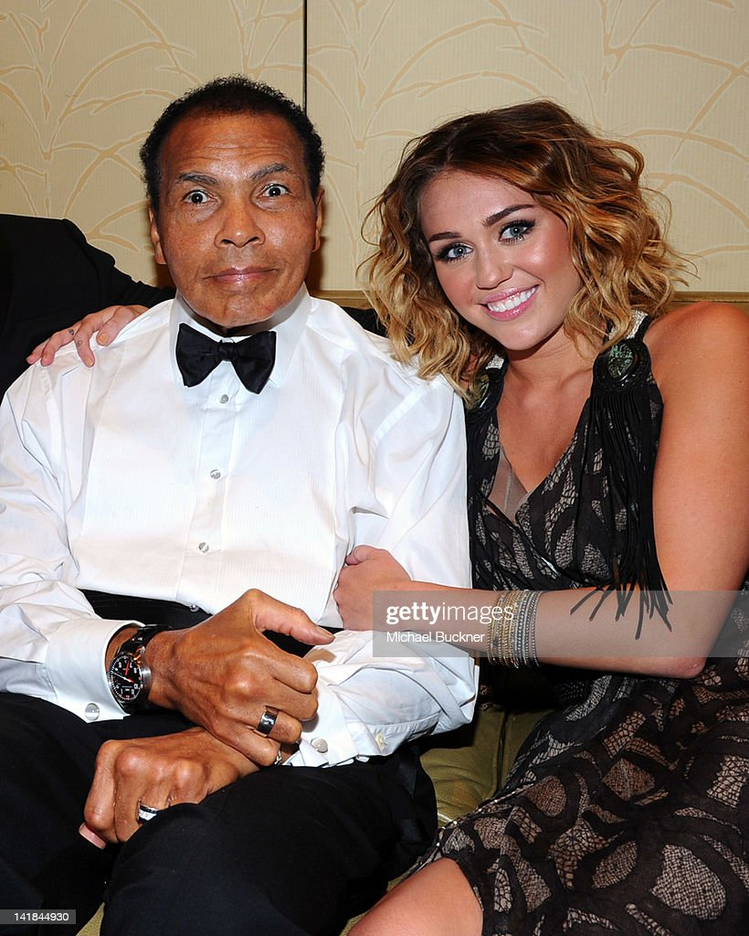Muhammad Ali (L) and singer Miley Cyrus pose backstage during Muhammad Ali's Celebrity Fight Night XVIII held at JW Marriott Desert Ridge Resort & Spa on March 24, 2012 in Phoenix, Arizona.