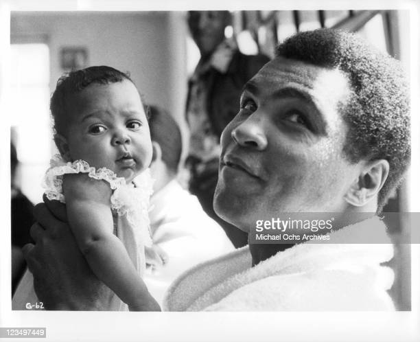 Muhammad Ali holding his baby daughter Hanna during the filming of 'The Greatest' released in 1977