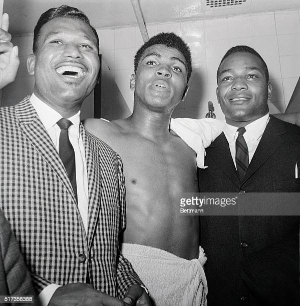 Muhammad Ali is joined in his dressing room by Sugar Ray Robinson and Jim Brown after defeating Doug Joes in a heavyweight contenders' fight