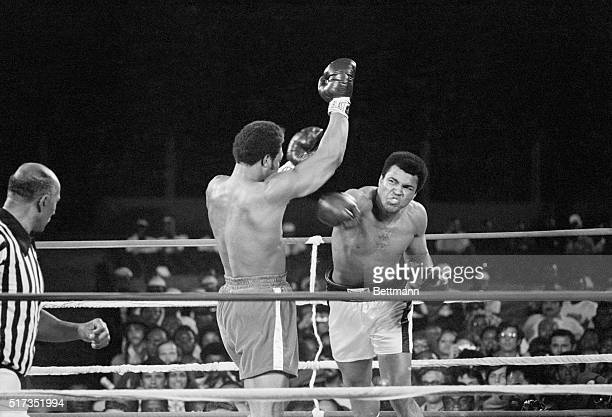 Muhammad Ali punches George Foreman during their world heavyweight title boxing match in 1974, while a referee looks on.