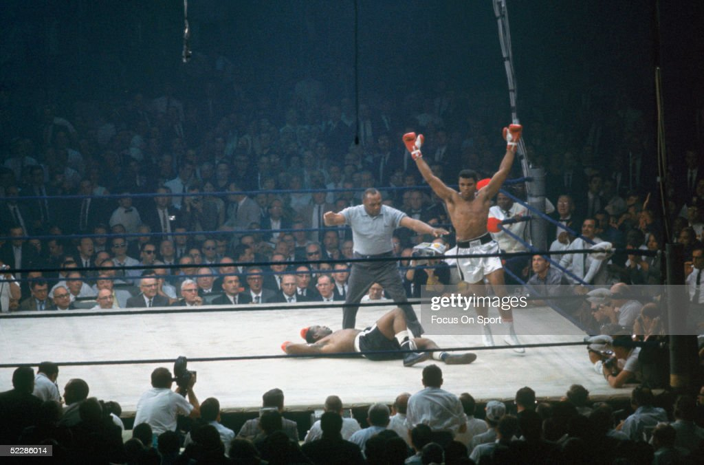 Muhammad Ali raises his arms in celebrations after putting down Sonny Liston in the canvas as referee Jersey Joe Walcott gives count in the first round of the World Heavyweight Title bout at St. Dominic's Hall on May 25, 1965 in Lewiston, Maine. This was Cassius Clay first fight after changing his name into Muhammad Ali.