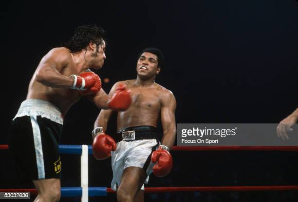 Muhammad Ali steps back from his opponent to avoid a punch during a boxing match