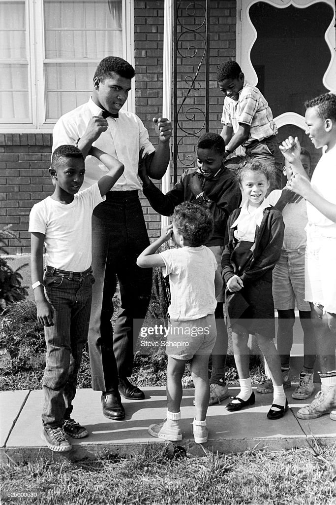 Muhammad Ali with neighborhood kids outside his mother's house in Louisville, Kentucky, including Yolanda 'Lonnie' Williams who would become his wife in 1986