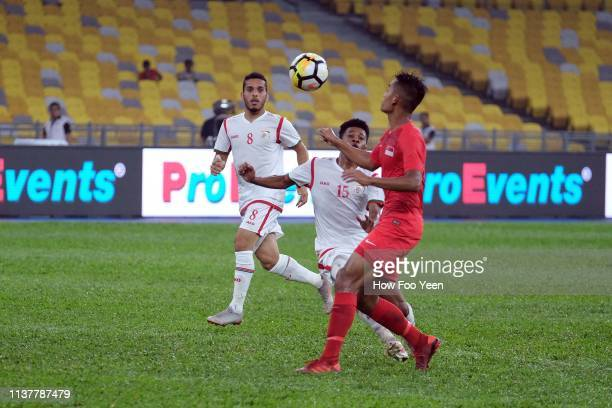 Muhammad Amirul Adli of Singapore challenges for the ball with Jameel Saleem Jameel of Oman during the Airmarine Cup final between Singapore and Oman...