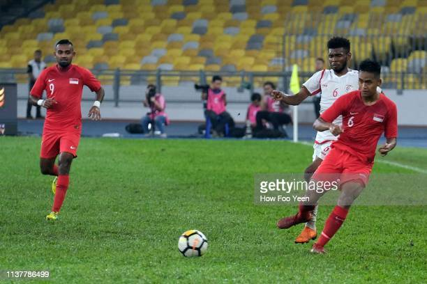 Muhammad Amirul Adli of Singapore shields the ball from Raed Ibrahim Saleh during the Airmarine Cup final between Singapore and Oman at Bukit Jalil...