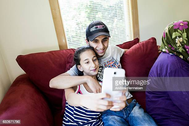 Muhammad and his younger sister Ojleen take a selfie on the couch of their new home on July 27 2015 in bloomfield Hills MI They keep in touch with...