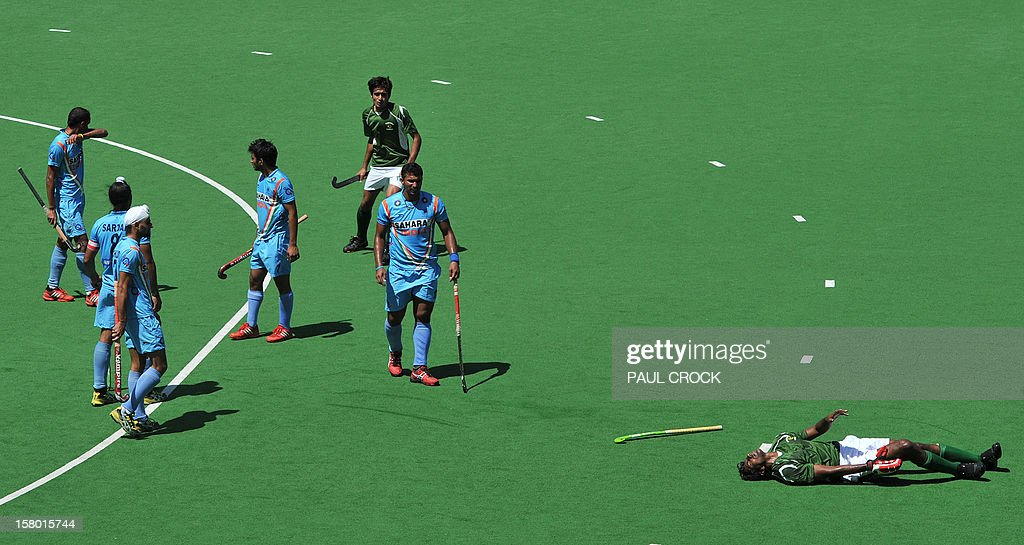 Muhammad Ateeq of Pakistan (R) lies on the pitch after giving away a penalty corner in the final seconds of the bronze medal match against India at the men's Hockey Champions Trophy tournament in Melbourne on December 9, 2012. IMAGE STRICTLY RESTRICTED TO EDITORIAL USE - STRICTLY NO COMMERCIAL USE. AFP PHOTO/Paul CROCK