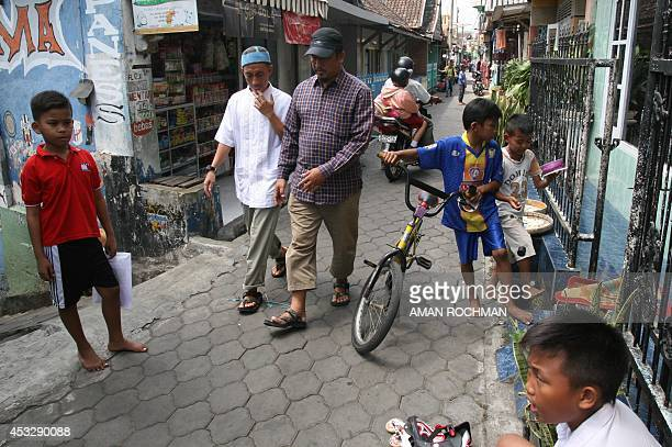Muhammad Cholili who was convicted of helping to orchestrate terror attacks on the resort island of Bali in 2005 walks home with his father in law...