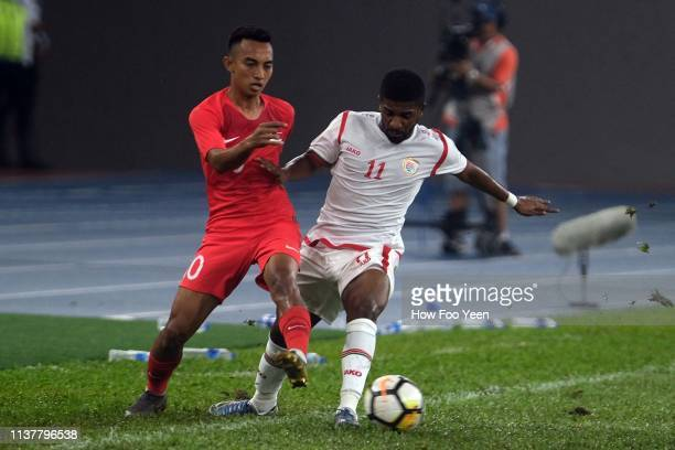 Muhammad Faris of Singapore in action with Muhammad Yasir during the Airmarine Cup final between Singapore and Oman at Bukit Jalil National Stadium...