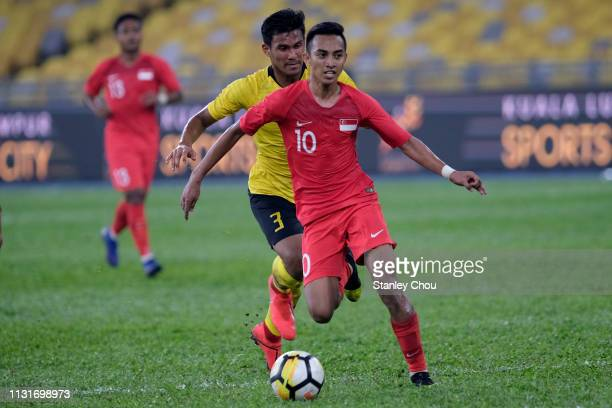 Muhammad Faris Ramli of Singapore competes for the ball with Shahrul Mohd Saad during the Airmarine Cup match between Malaysia and Singapore at Bukit...