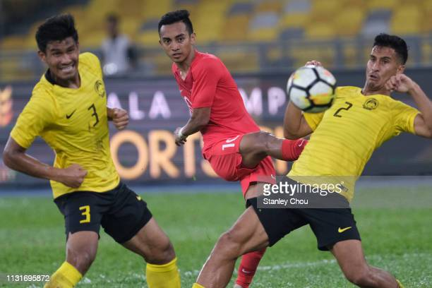 Muhammad Faris Ramli of Singapore shoots while Shahrul Mohs Saad and Matthew Thomas of Malaysia look on during the Airmarine Cup match between...