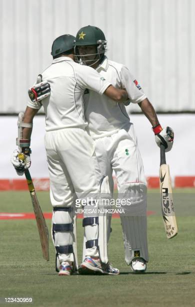 Muhammad Hafeez is congratulated by team mate Azhar Ali after reaching 100 runs on the third day of the test match between Zimbabwe and Pakistan at...