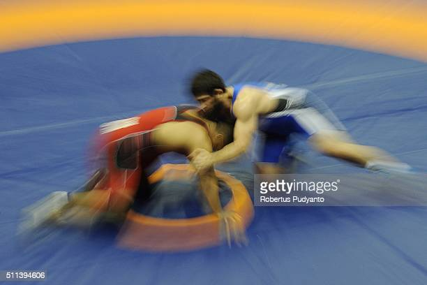 Muhammad Hidayat Bin Haron of Singapore competes against Magomed Musaev of Kyrgyzstan in the Men's Freestyle Senior 97 kg qualification match during...