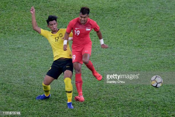 Muhammad Irfan of Malaysia challenges Muhammad Khairul of Singapore during the Airmarine Cup match between Malaysia and Singapore at Bukit Jalil...