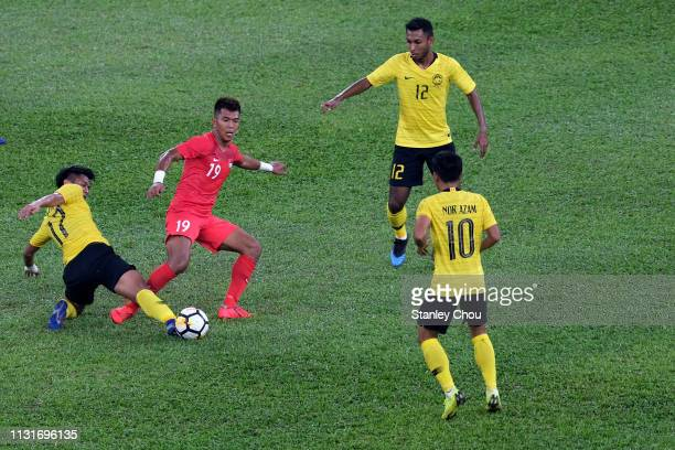 Muhammad Irfan of Malaysia competes for the ball with Muhammad Khairul of Singapore during the Airmarine Cup match between Malaysia and Singapore at...