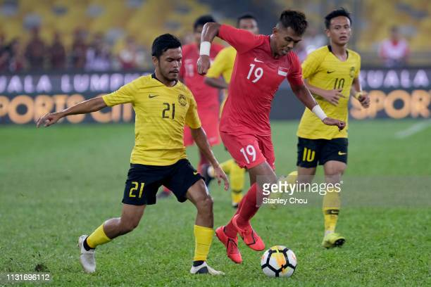Muhammad Khairul of Singapore holds off Narizul Naim of Malaysia during the Airmarine Cup match between Malaysia and Singapore at Bukit Jalil...