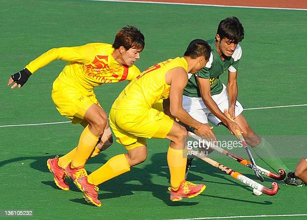 Muhammad Rizwan of Pakistan vies for the ball with Chinese players during the fourth and last field hockey match between Pakistan and China in Lahore...