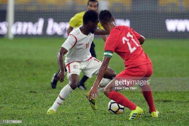 Muhammad Safuman of Singapore checks Raed Ibrahim Saleh of Oman during the Airmarine Cup final between Singapore and Oman at Bukit Jalil National...