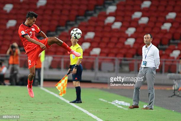 Muhammad Shakir Bin Hamzah of Singapore tries to keep the ball in play as Cambodia coach Lee Tae Hoon of South Korea looks on during the 2018 FIFA...