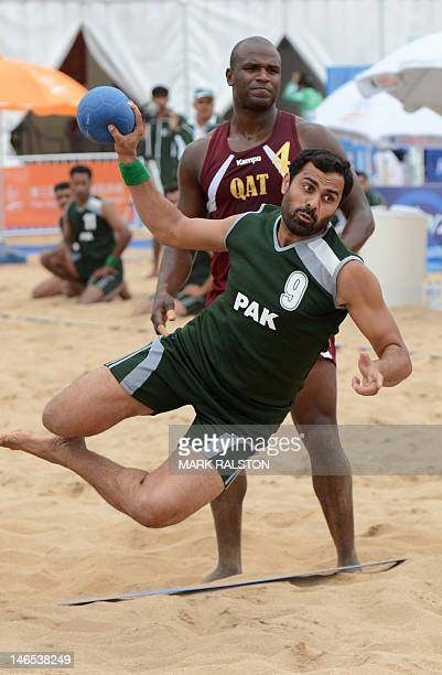 Muhammad Sohaib of Pakistan throws for a goal as Mabrouk Hassan of Qatar looks on during their men's beach handball match which Qatar won 20 at the...