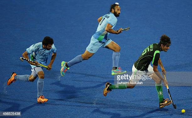 Muhammad SR Rivwan runs with the ball as Sardar Singh and Chandanda Aiyanna Nikkinmatch of India give chase during the men's hockey gold medal match...