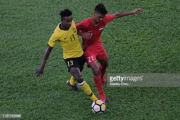Muhammad Sumareh of Malaysia battles Muhammad Safuwan of Singapore during the Airmarine Cup match between Malaysia and Singapore at Bukit Jalil...