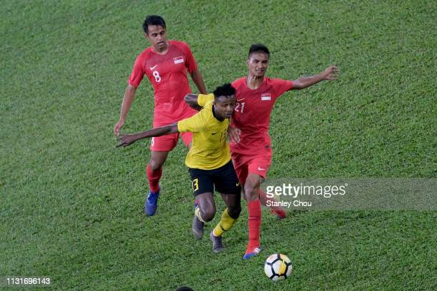 Muhammad Sumareh of Malaysia competes for the ball with Muhammad Safuwan of Singapore during the Airmarine Cup match between Malaysia and Singapore...