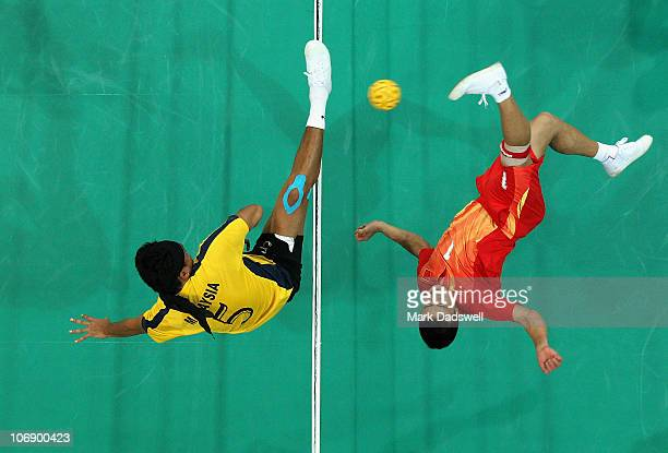 Muhammad Sya Husin of Malaysia attempts to block the shot from Wang Jian of China in the Sepaktakraw Men's Team Preliminary Group B match between...