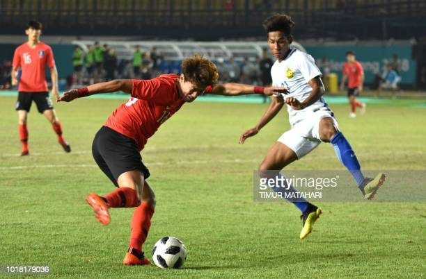 Muhammad Syazwan Andik Mohd Ishak of Malaysia vies for the ball with Hwang Ui Jo of South Korea during the men's football preliminary group E match...