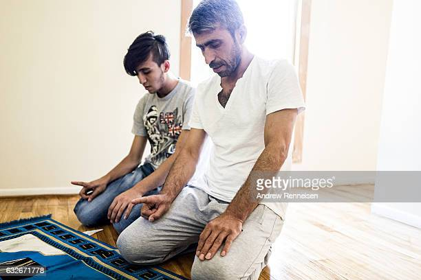 Muhammad Tanbal prays with his son also named Muhammad in their new home on July 27 2015 in Bloomfield Hills Michigan The family says they felt they...