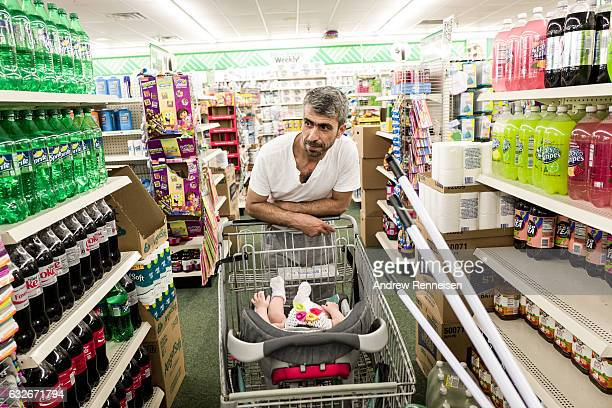 Muhammad Tanbal shops with his baby daughter Maryam at the discount store close to their new home on July 27 2015 in Bloomfield Hills Michigan Each...