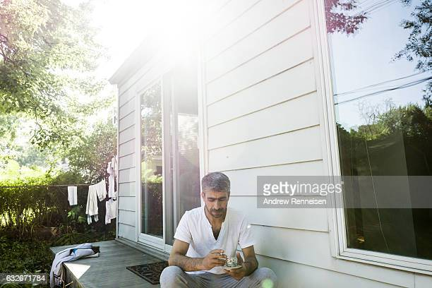 Muhammad Tanbal smokes a cigarette and sips coffee on the back porch of his new home on July 27 2015 in Bloomfield hills Michigan He says he is eager...