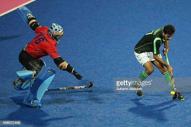 Muhammad Waqas of Pakistan tries to get past Sreejesh Parattu Raveendran of India during the penalty shootout in the men's hockey gold medal match on...