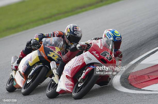 Muhammad Zulfahmi Khairuddin of Malaysia leads Sandro Cortese of Germany and Red Bull KTM Ajo during the Moto3 race during the MotoGP Of Malaysia at...