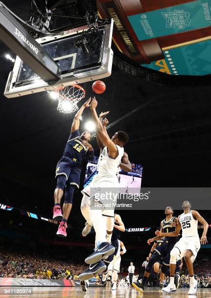 MuhammadAli AbdurRahkman of the Michigan Wolverines drives to the basket against Phil Booth of the Villanova Wildcats in the first half during the...