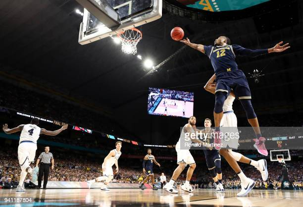 MuhammadAli AbdurRahkman of the Michigan Wolverines drives to the basket against Jalen Brunson of the Villanova Wildcats in the first half during the...