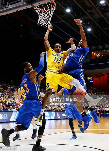 MuhammadAli AbdurRahkman of the Michigan Wolverines goes up against Brandon Swannegan ans Shaquille Harrison of the Tulsa Golden Hurricane during the...