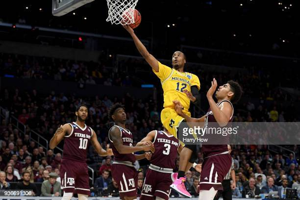 MuhammadAli AbdurRahkman of the Michigan Wolverines goes up for a shot against Tyler Davis of the Texas AM Aggies in the first half in the 2018 NCAA...