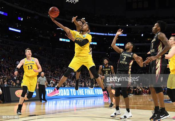 MuhammadAli AbdurRahkman of the Michigan Wolverines goes up for a shot ahead of Terance Mann of the Florida State Seminoles in the second half in the...