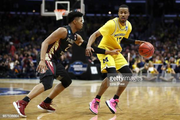 MuhammadAli AbdurRahkman of the Michigan Wolverines is defended by MJ Walker of the Florida State Seminoles during the first half in the 2018 NCAA...