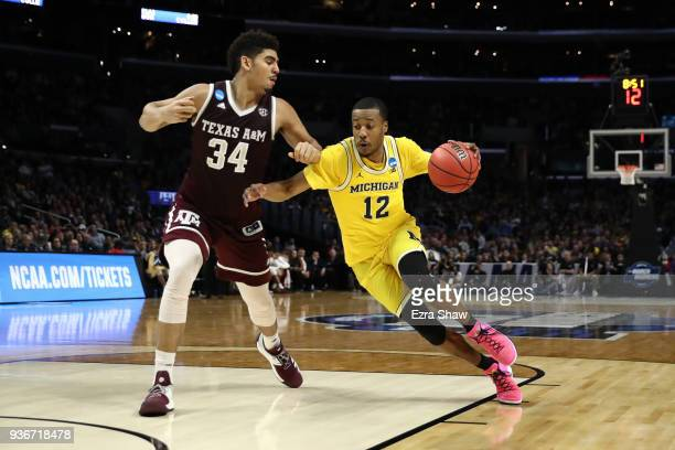 MuhammadAli AbdurRahkman of the Michigan Wolverines is defended by Tyler Davis of the Texas AM Aggies during the second half in the 2018 NCAA Men's...