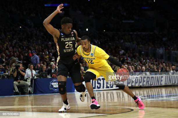 MuhammadAli AbdurRahkman of the Michigan Wolverines is defended by Mfiondu Kabengele of the Florida State Seminoles during the first half in the 2018...