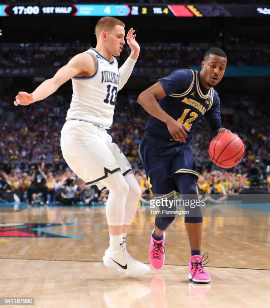MuhammadAli AbdurRahkman of the Michigan Wolverines is defended by Donte DiVincenzo of the Villanova Wildcats in the first half during the 2018 NCAA...