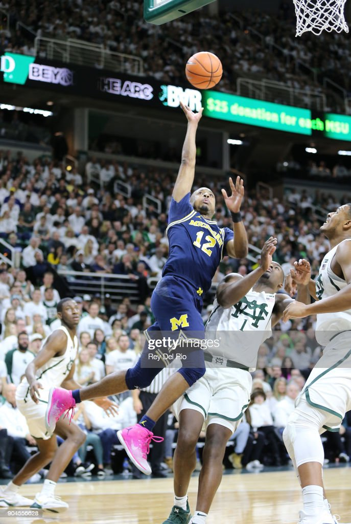 Muhammad-Ali Abdur-Rahkman #12 of the Michigan Wolverines shoots the ball while defended by Joshua Langford #1 of the Michigan State Spartans at Breslin Center on January 13, 2018 in East Lansing, Michigan.