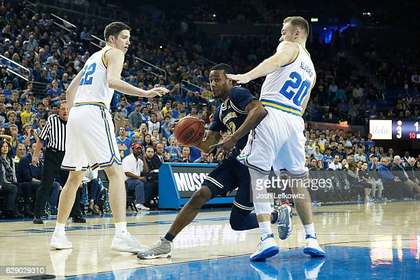 MuhammadAli AbdurRahkman of the University of Michigan drives past Bryce Alford of the UCLA Bruins and TJ Leaf at Pauley Pavilion during their game...