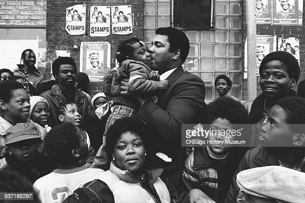 Muhammed Ali kissing a young girl Chicago Illinois 1983 He is standing in a crowd of people campaigning for Harold Washington on North Avenue near...