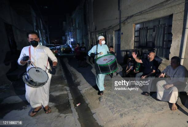 Muhammed Muhsin and Raid Kaabi wearing protective masks and gloves play drum to wake public up for sahur meal on a street during Ramadan amid...