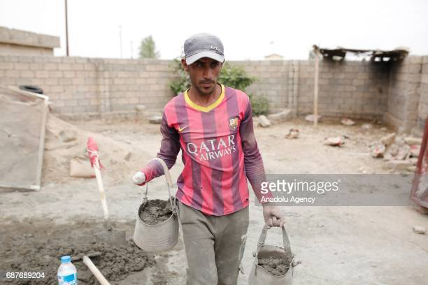 Muhammed, one of the two siblings who was accused of theft and whose right hand was cut off by Daesh, carries cement buckets in Ninova, Iraq on May...