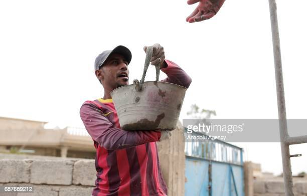 Muhammed, one of the two siblings who was accused of theft and whose right hand was cut off by Daesh, carries a cement bucket in Ninova, Iraq on May...