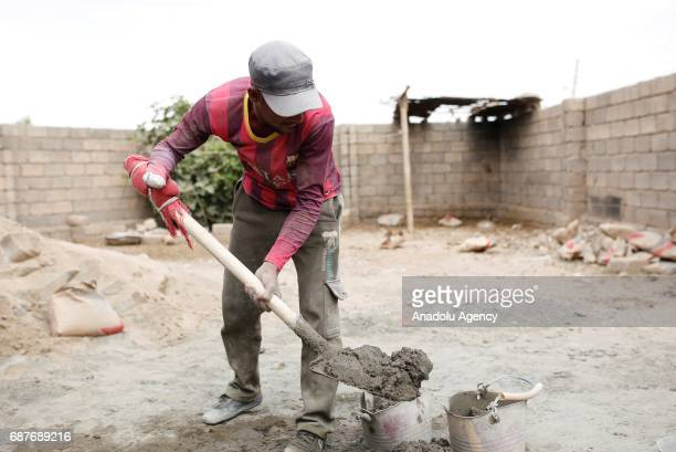 Muhammed, one of the two siblings who was accused of theft and whose right hand was cut off by Daesh, mixes cement in Ninova, Iraq on May 23, 2017....